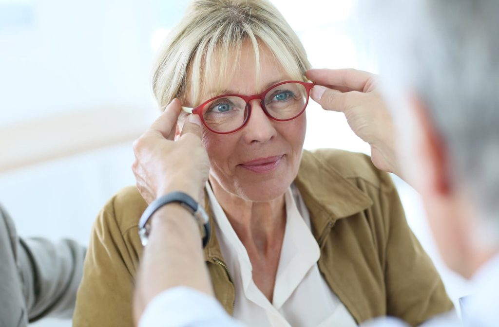 woman getting glasses from her optometrist