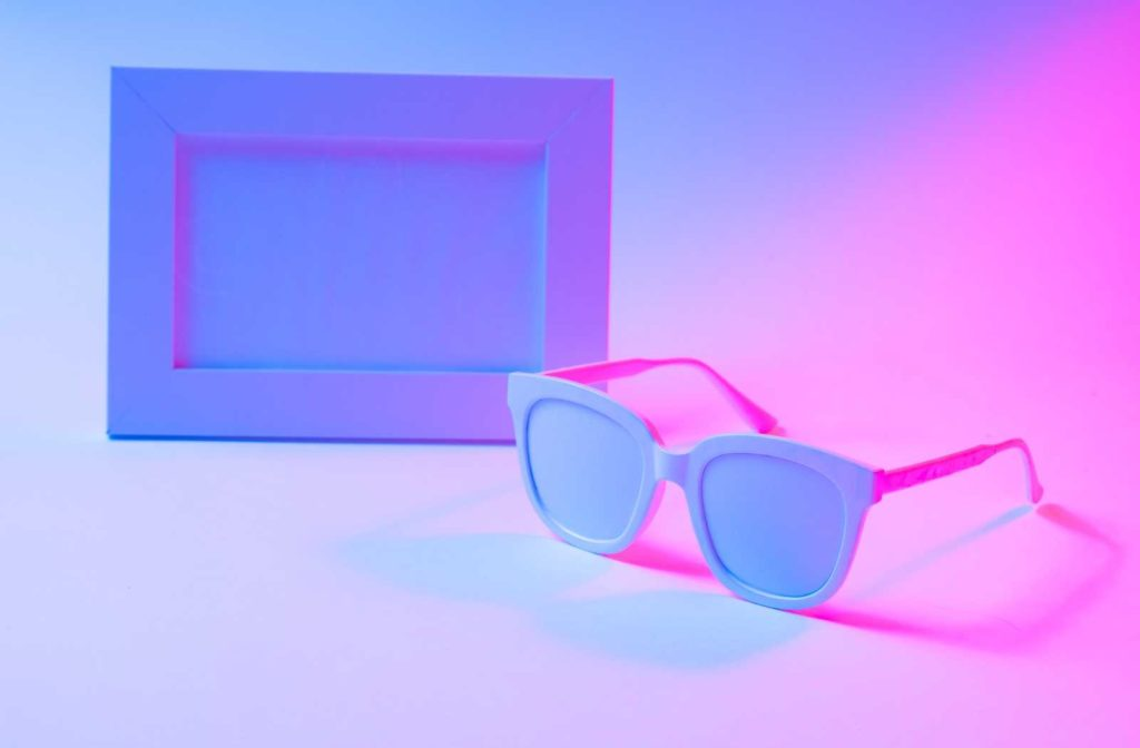 conceptual white eyeglass and picture frames backlit by neon colours